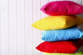 Colorful Pillows On A White Wall Paneling Background Stock Photo ...